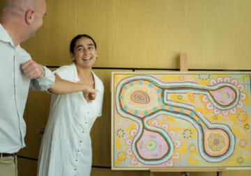 Artist Jasmin Craqciun and Newcastle Regional Manager Jason McCosker bump elbows infront of the artwork Growth.